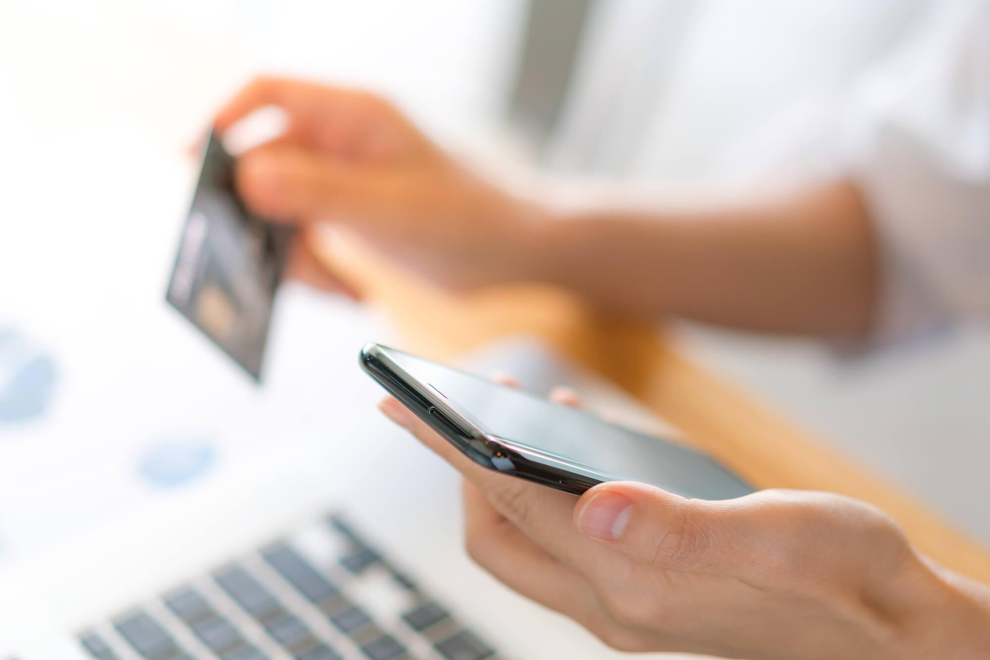 Pessoa com celular e cartão de crédito
