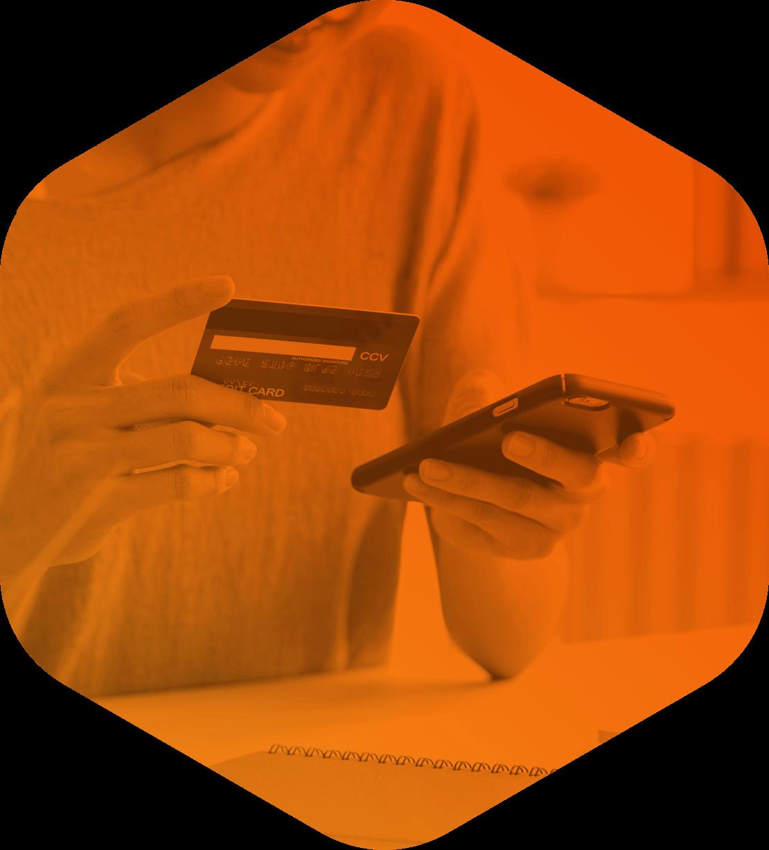 Mulher segurando um celular e um cartão de crédito