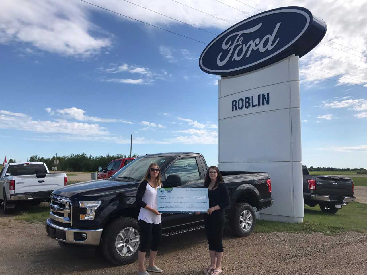 Outside the Ford dealership in Roblin with two women holding a large cheque in front of a Ford truck