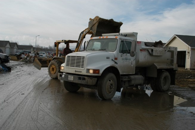 A large truck and a bulldozer clearing debris.