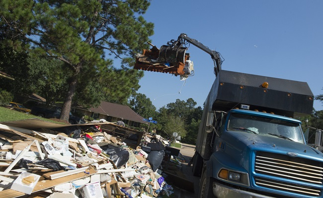 A disposal truck lifts debris.