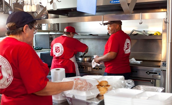 Salvation Army volunteers prepare meals for residents displaced to shelters.