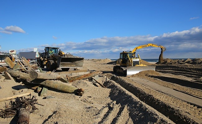 Heavy machinery is used to assist in the recovery process of debris removal and dune replenishment along this coastline.