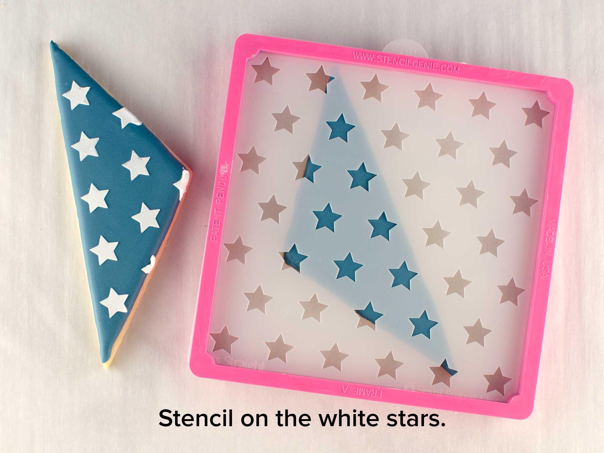 stencils white stars into cookies