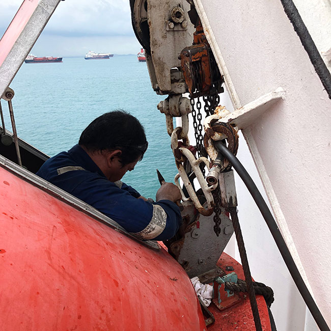 Technician chipping on lifeboat release hook