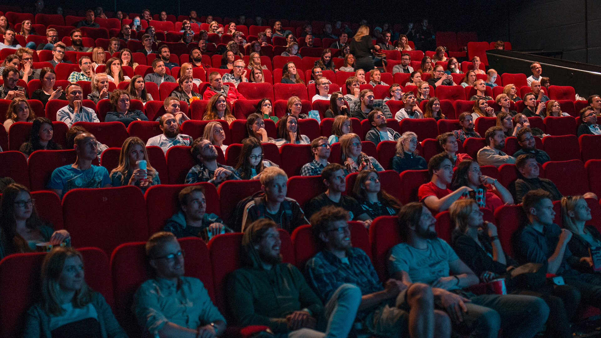 A cinema full of people expressing different emotions