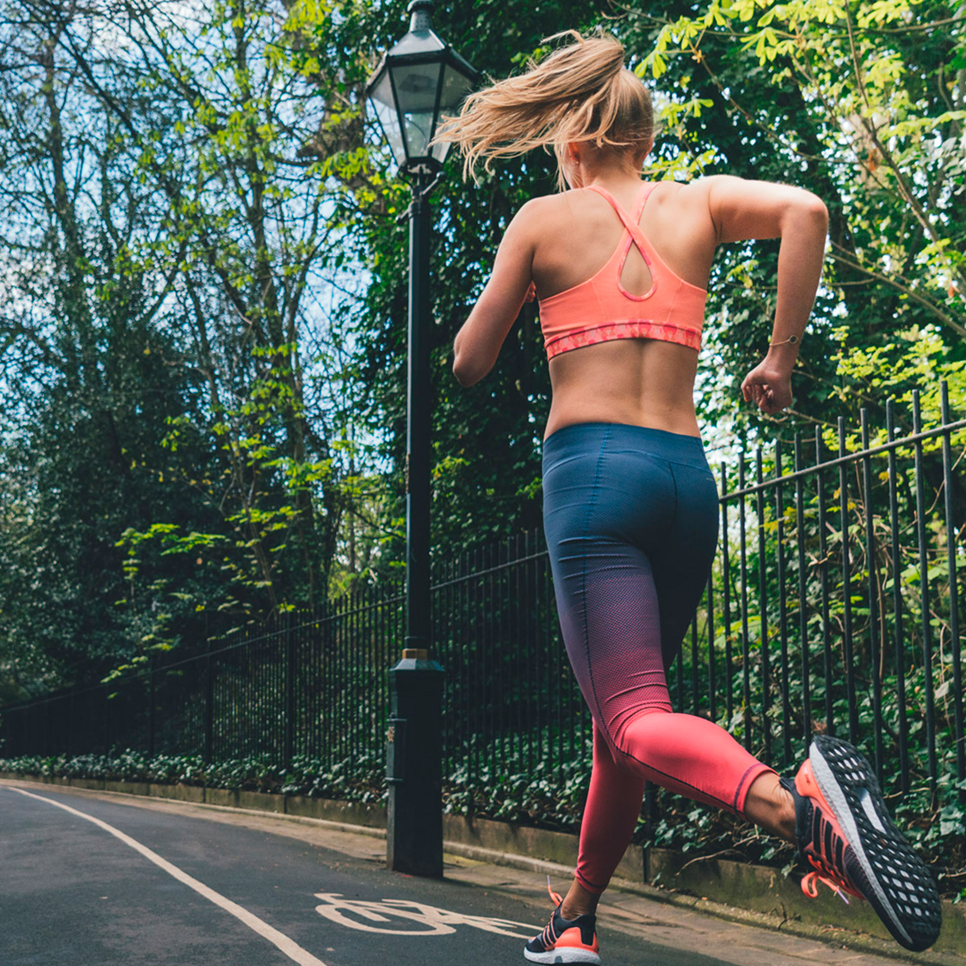 A woman wearing sports gear running along a path next to a park