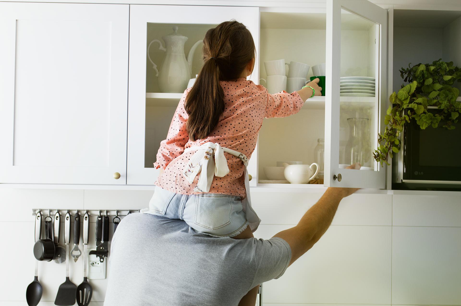 Pai com sua filha em seus ombros tentando alcançar  uma caneca