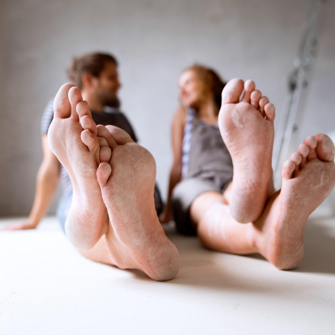 Homem e mulher sentados no chão com os pés descalços e empoeirados
