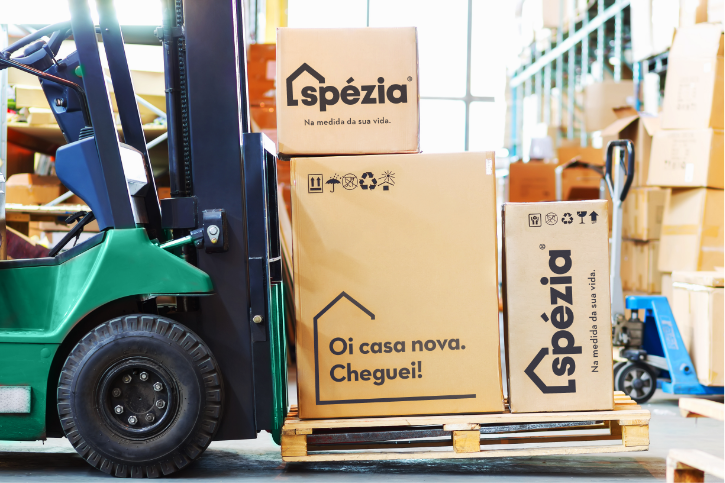 Empilhadeira carregando três caixas com a marca da Spézia