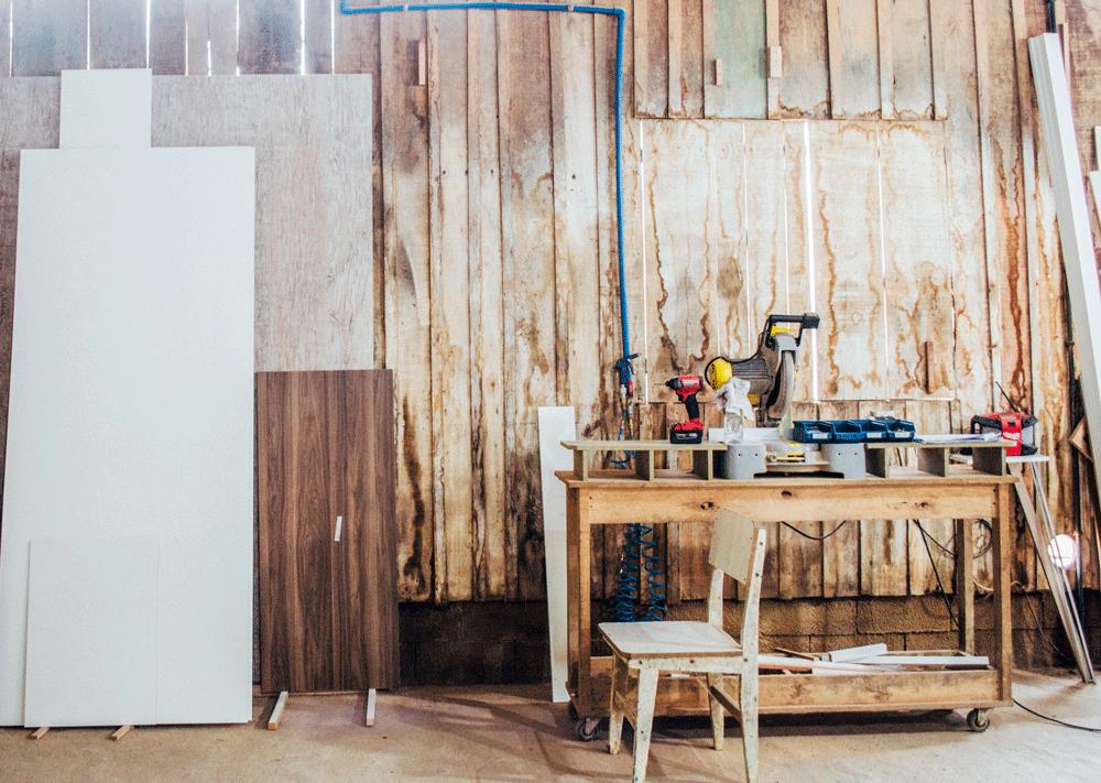 Galpão de marcenaria com ferramentas, balcão e uma cadeira.