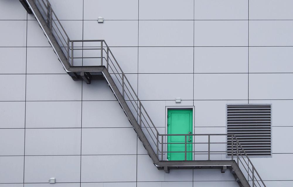 Escadaria externa de um prédio e uma porta verde.