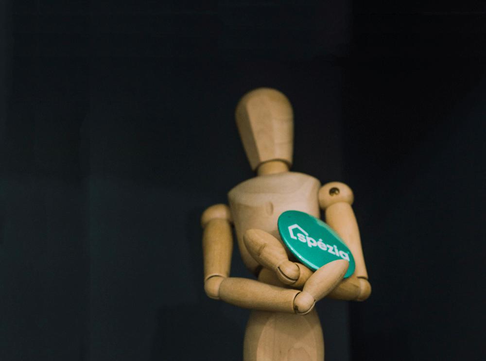 Boneco de madeira segurando um broche da nova marca Spézia