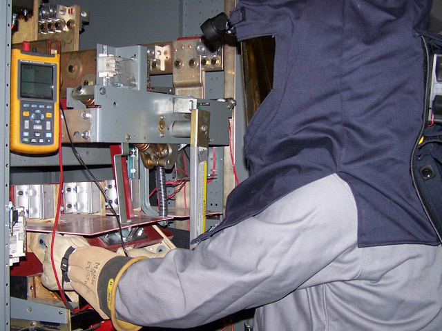 Electrician in a protective suit doing maintenance on an installation.