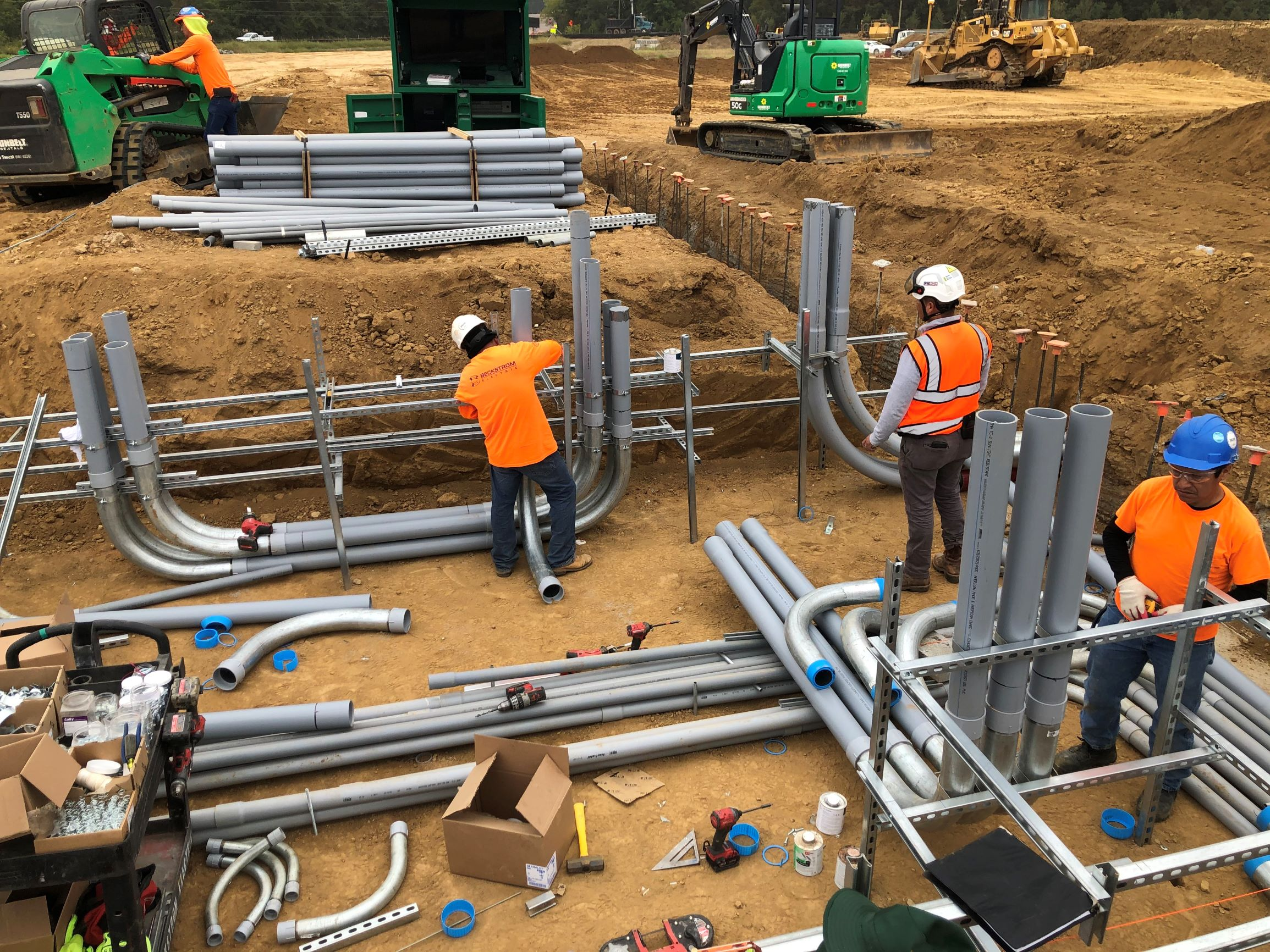 Electricians installing conduit in a pit before concrete is poured