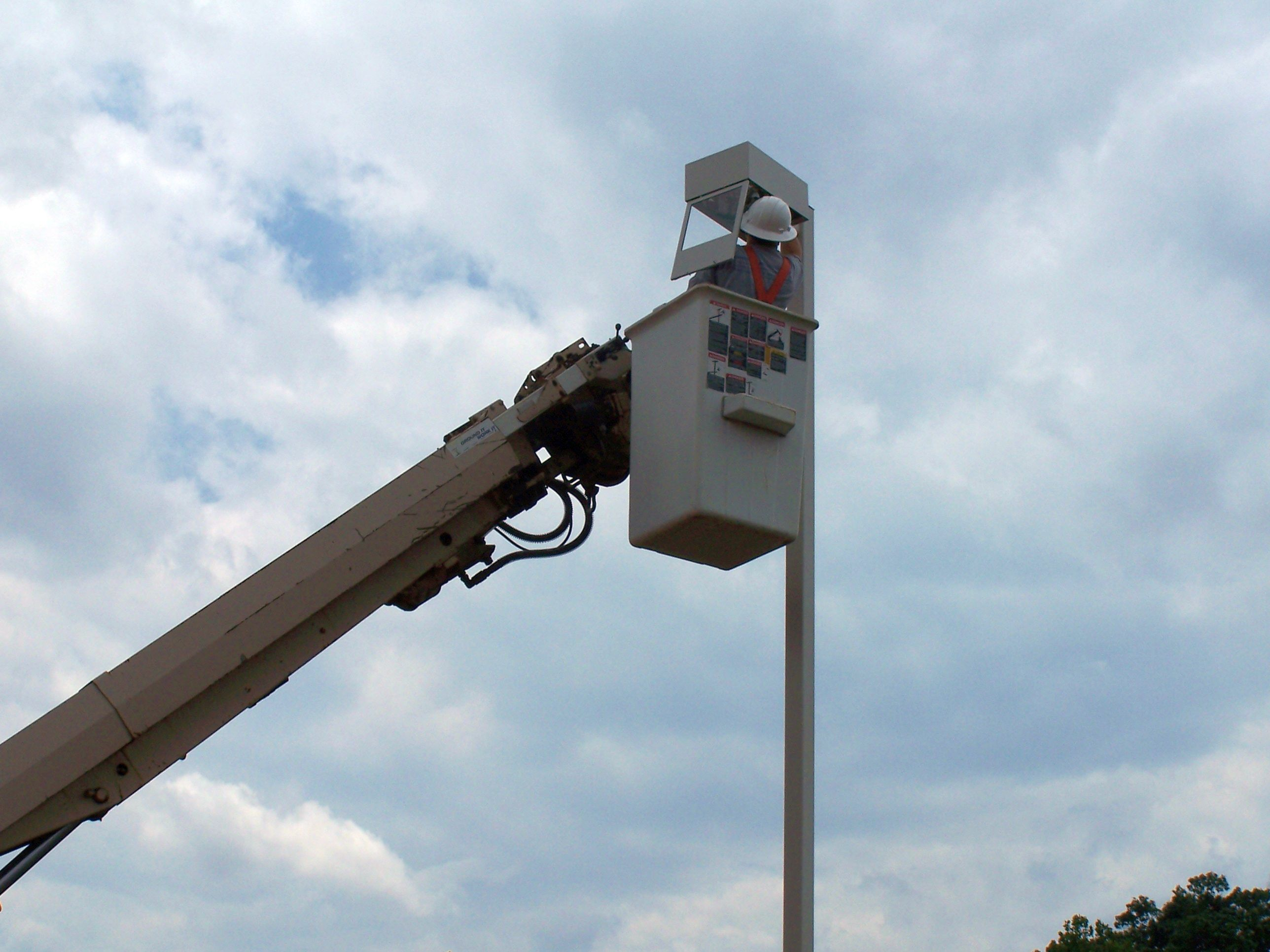 Electrician wiring a Parking Lot Lighting Pole