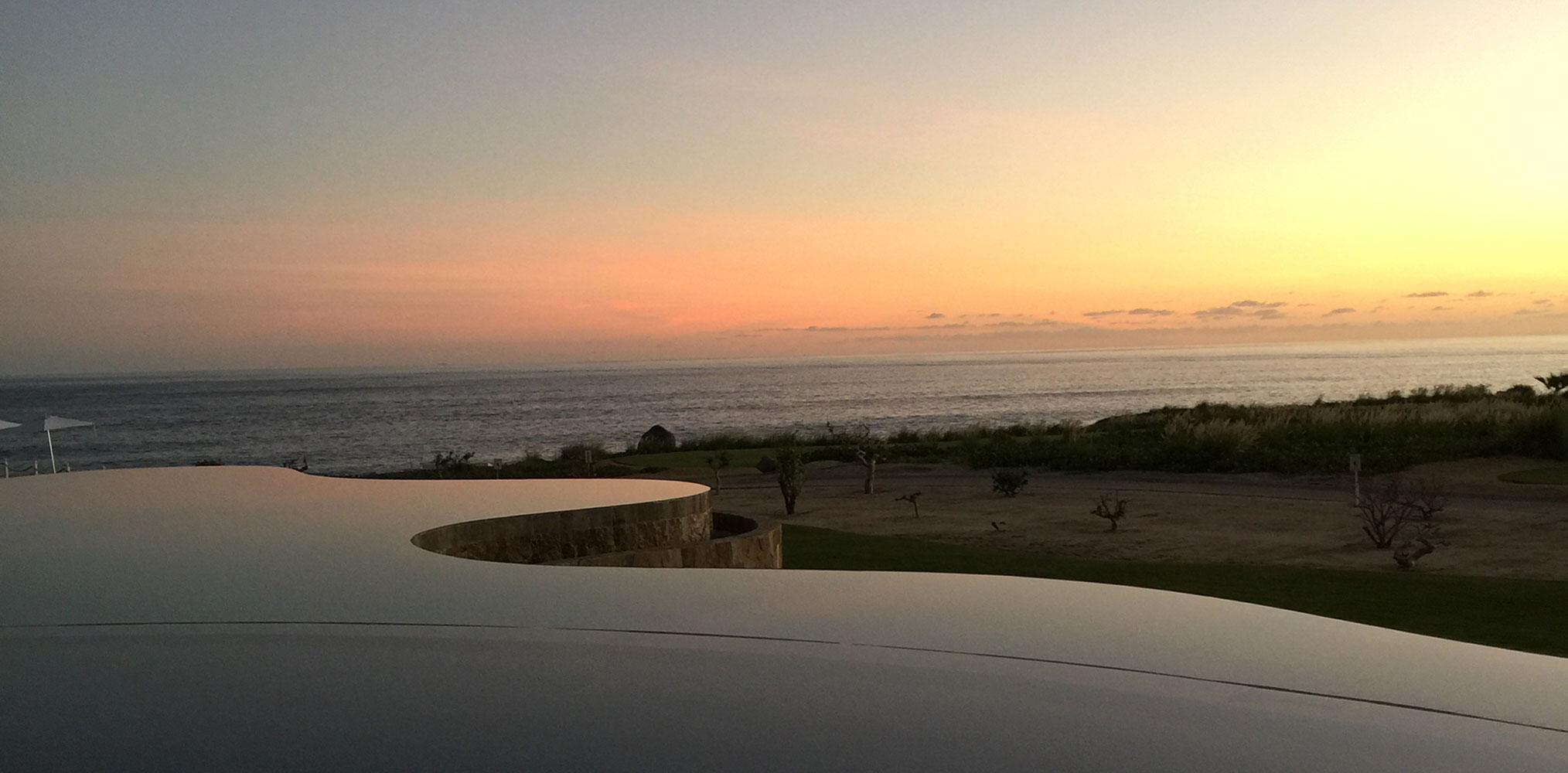 Sunset overlooking an infinity pool and the ocean