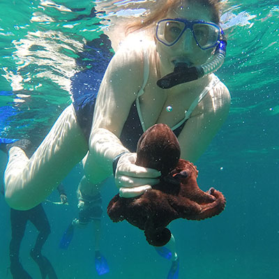 Picture of our CEO Shanelle holding a baby octopus while snorkeling