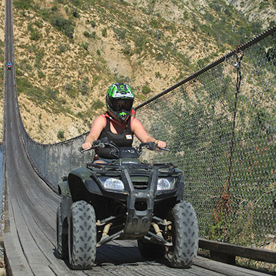 Our CEO Shanelle driving an ATV over a suspension bridge