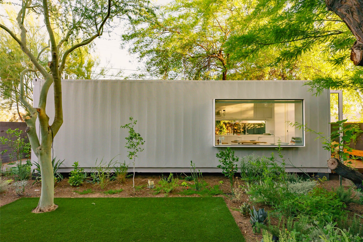 A parallel facing view of a rectilinear, white, modular home sitting in a plush garden with trees and tropical plants.