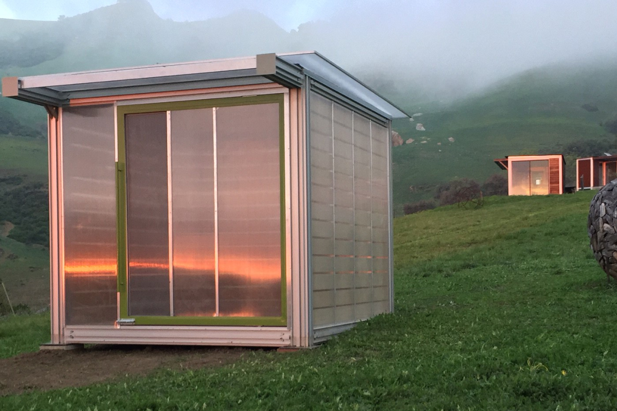 The exterior of a modular home perched on an open hill, with a glass facade that reflects the sunset.