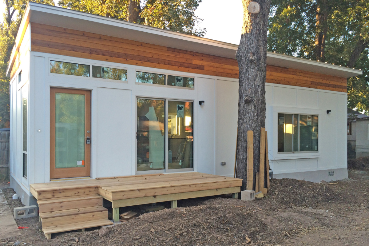 A modular home, with steps, porch, windows, and doors visible, m and an exterior of wood and white walls.