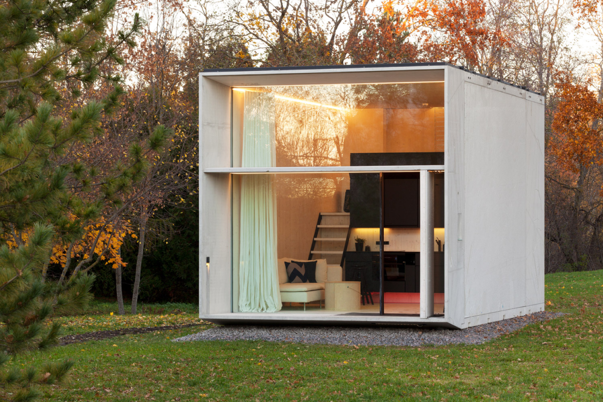 A modern, white modular home situated in a park, with a wall-sized window offering views of the interior.