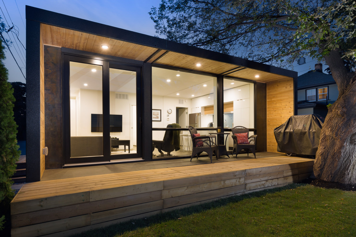 A modular home, with chairs on the deck and a window showing the illuminated interior.