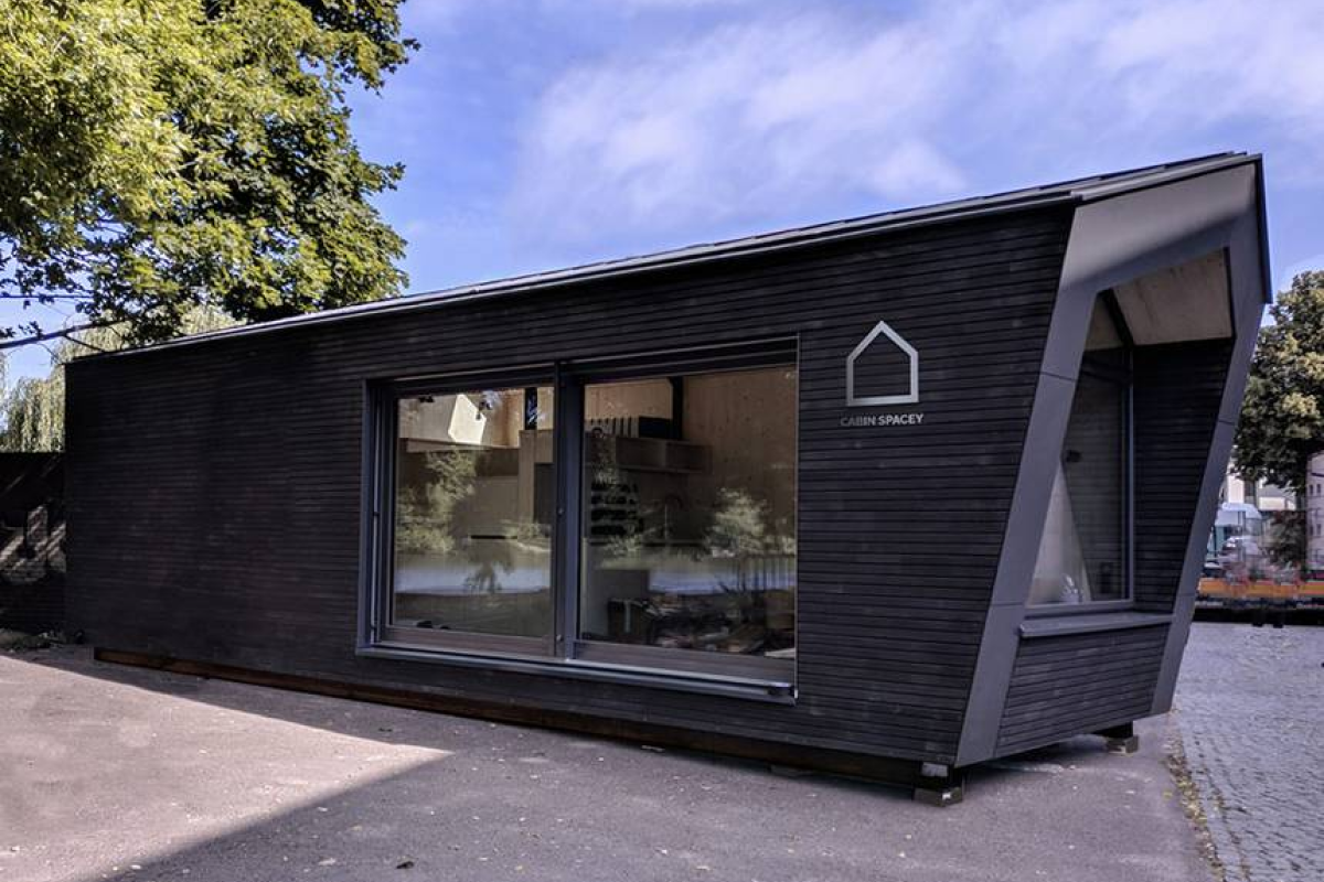 A close up of a modular home with black exterior material and a pitched roof, sitting in an urban center.