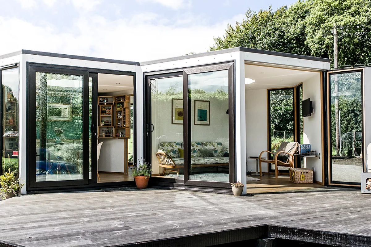 A Hive Haus modular home consisting of two modules, each of which have windows, located on a wooden deck with trees and sky in the background.