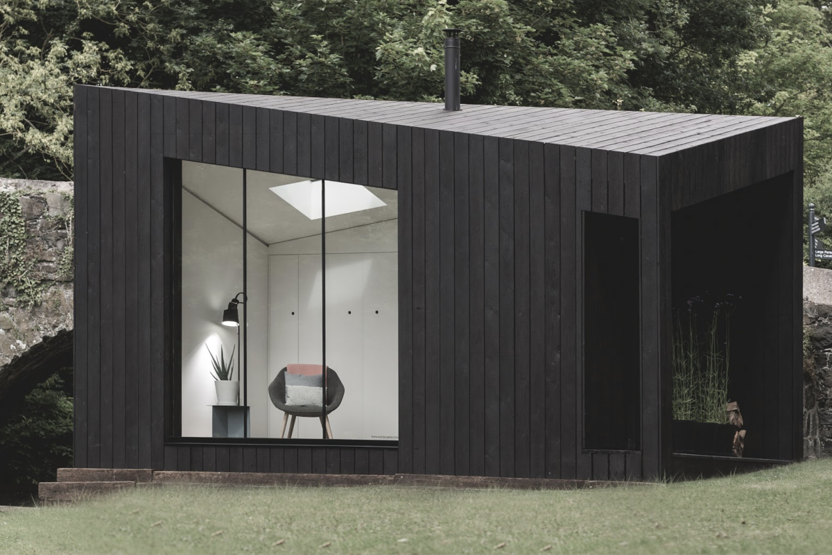 A modular home with a charcoal exterior and an angled roof sits in a grass field