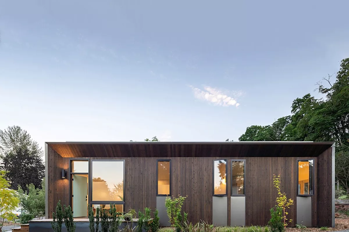 A top-down view of a modular home, with solar panels on the roof and an integrated hardwood porch, located in a garden.
