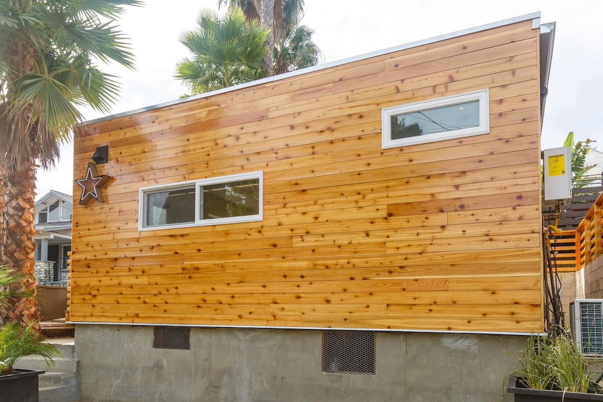 The long end of a modular home, covered with wooden exterior siding, and situated in a backyard with other homes visible in the backdrop.