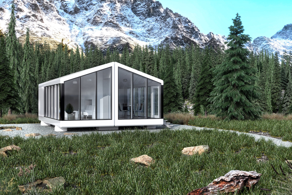 A frontal view of an all glass modular home with white walls sits within a green forest and a mountain behind.