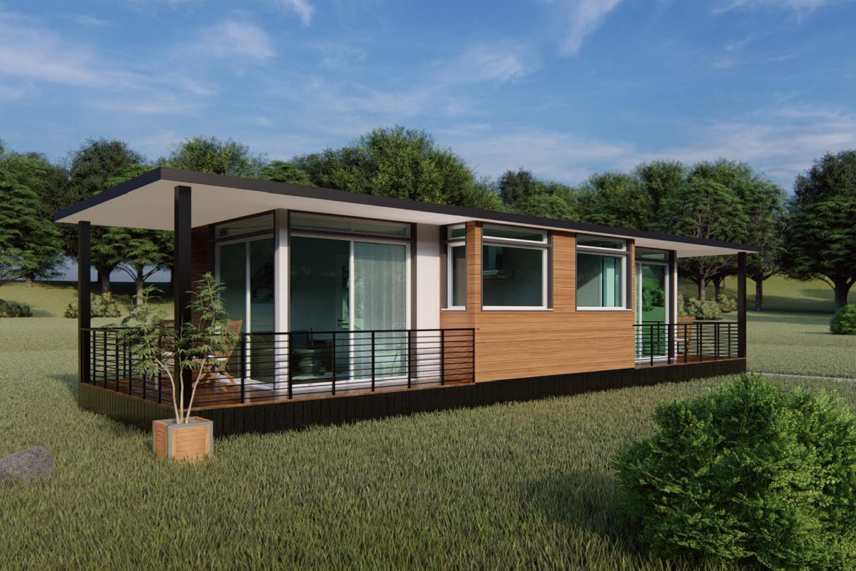 A modular home located in a field, with large glass windows, wooden siding, and a deck with chairs all visible.