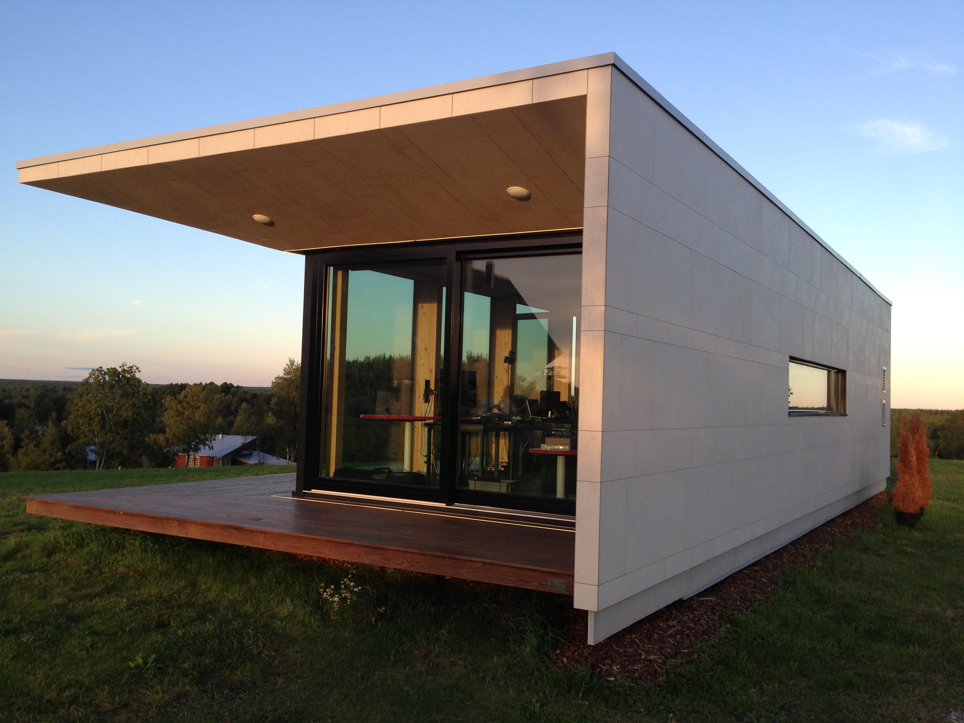 A modular home with a glass facade sits in a field with trees in the background