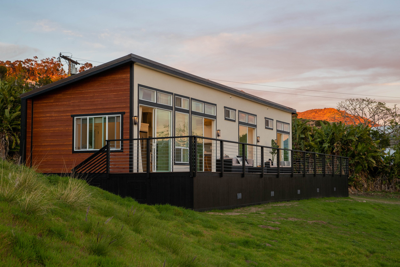 A modular home at sunset, with a black deck, wooden exterior, and large glass widows all visible.