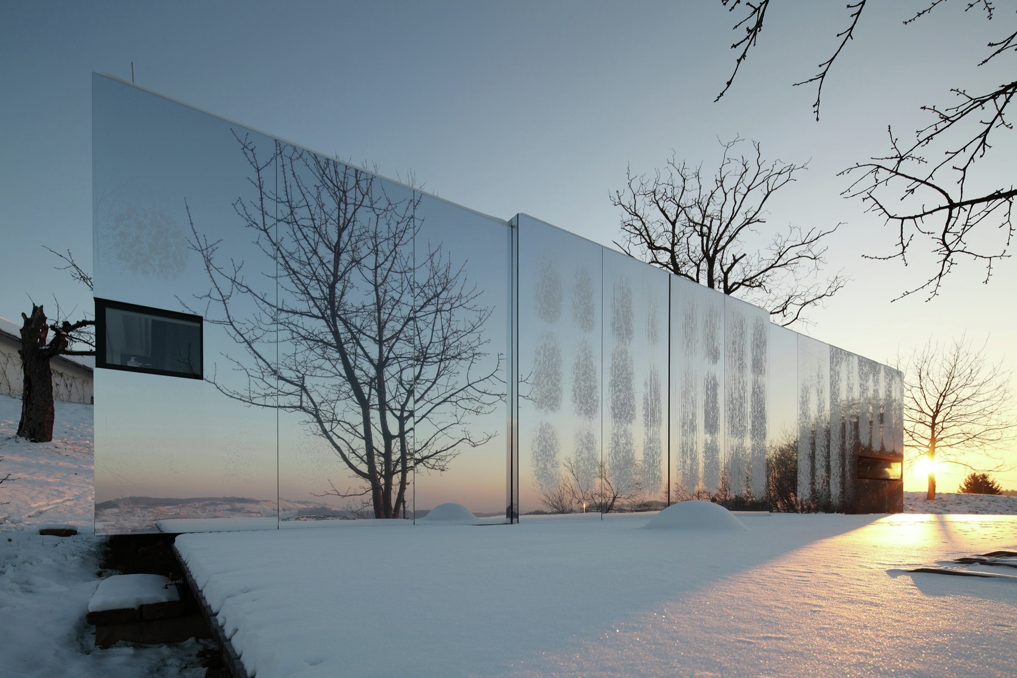 A modular home made from reflective materials and mirrors that is reflecting the surrounding landscape, which is trees in the winter.