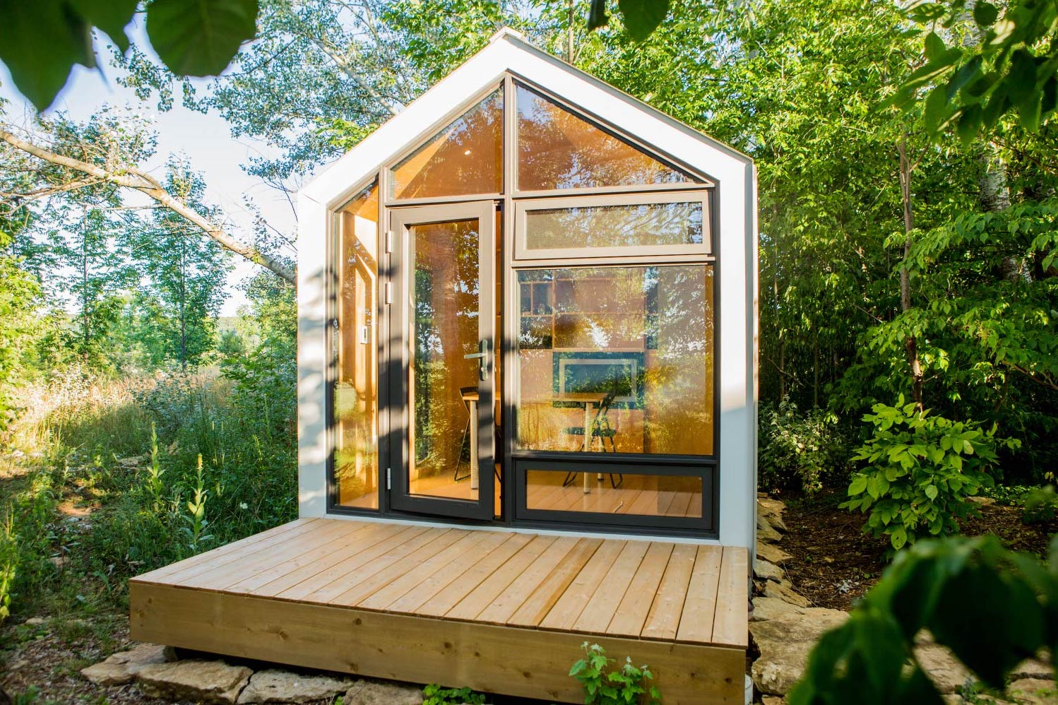 A tiny home viewed from above, with a wooden interior, glass wall, and black exterior on display.