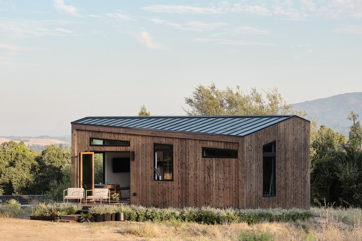 A large modular home with a porch, covered with an exterior or finished hardwood, and situated in a field.