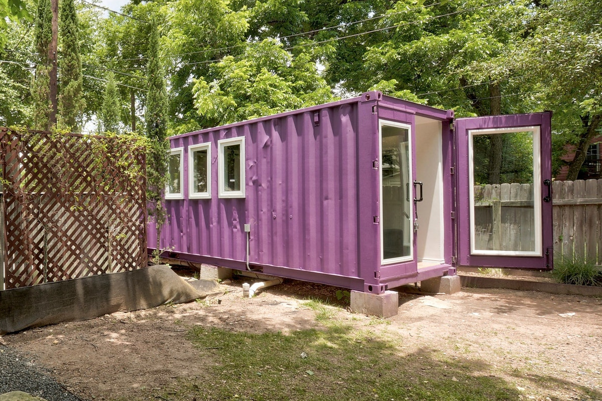 A purple shipping container home, with one of the doors open, situated in a backyard with trees and a fence.