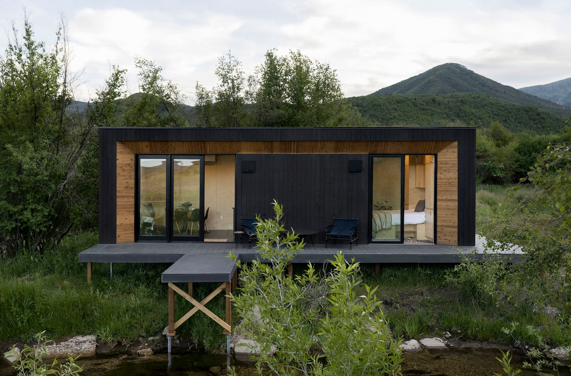 An aerial shot of a modular home set up in a backyard, with an integrated porch, large windows, and black wooden exterior visible as well as some grass.