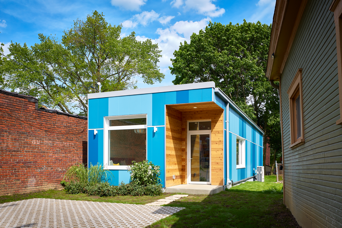 A modular home located in a back garden, with wooden walls painted blue, a window, and a door visible.