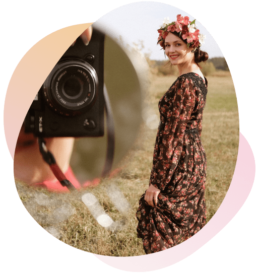 Girl in a red flower dress posing for photos in front of a camera.