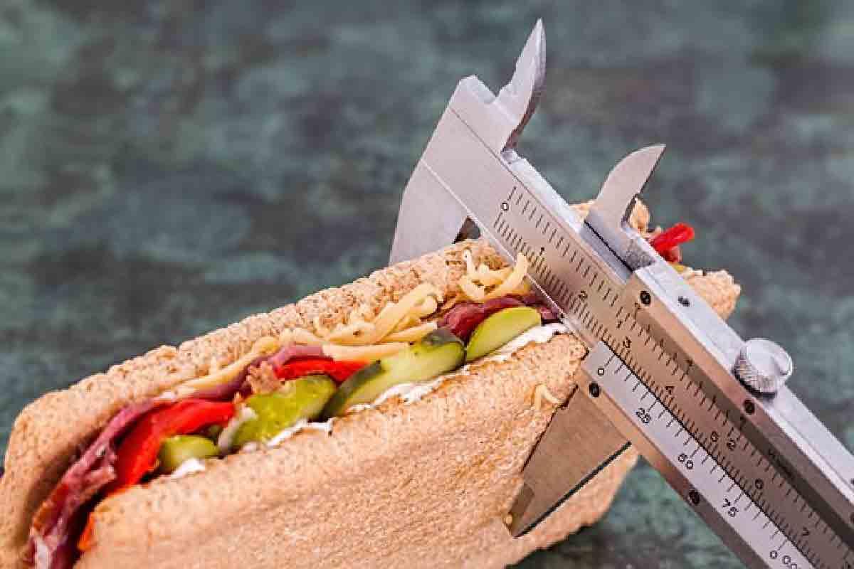 un sandwich viene misurato con un metro in acciaio