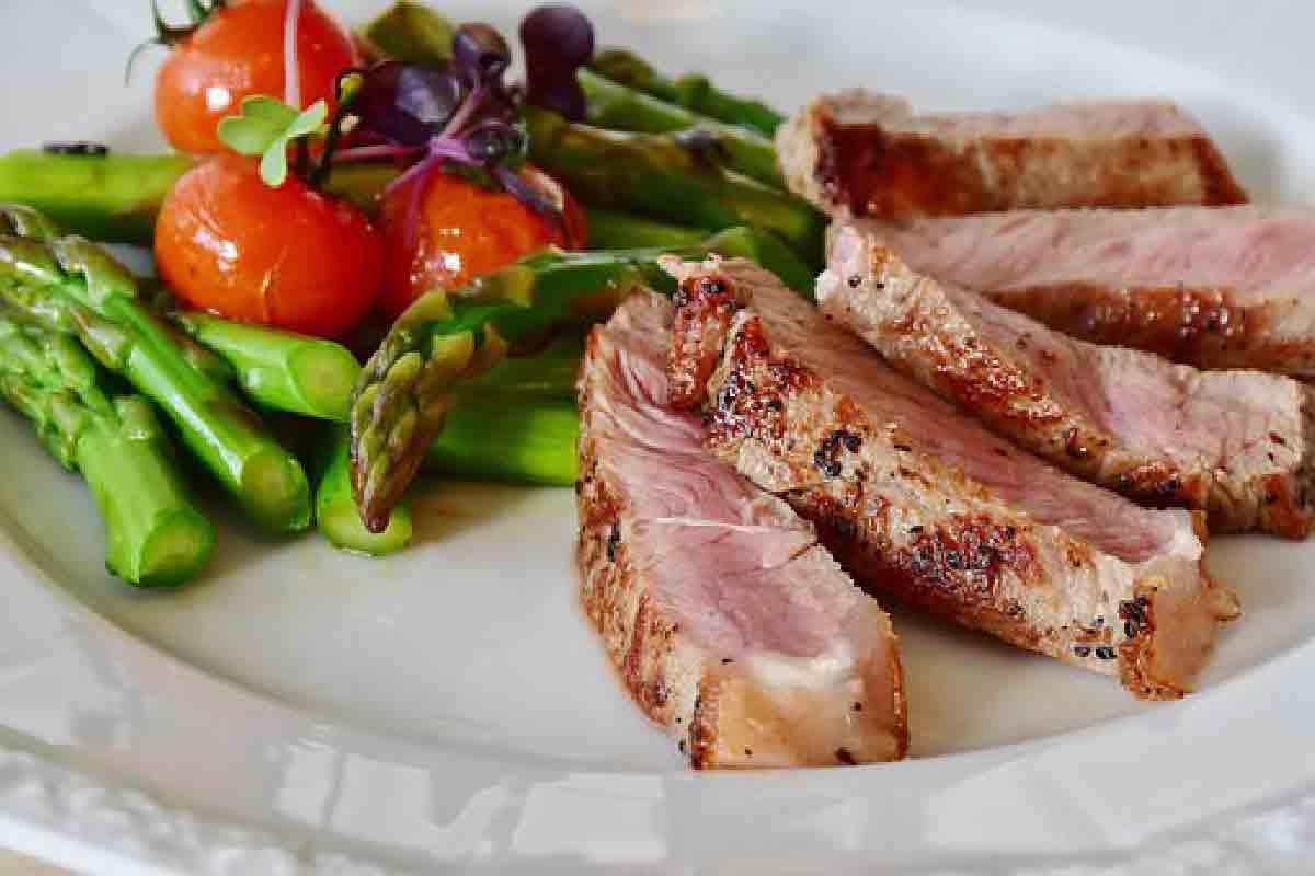 un piatto di carne media cottura con asparagi e pomodorini in primo piano