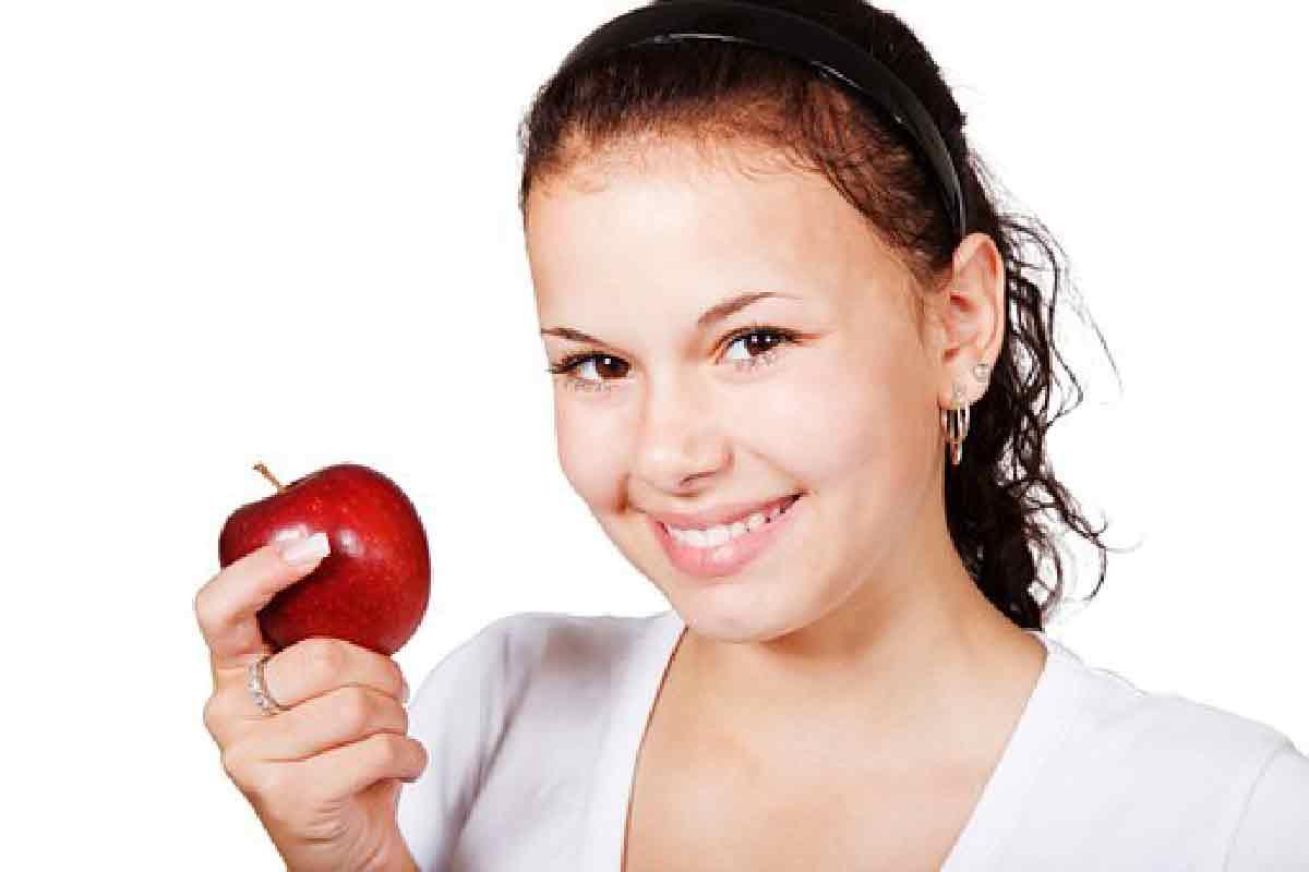 una donna ripresa mentre sorride tenendo una mela rossa