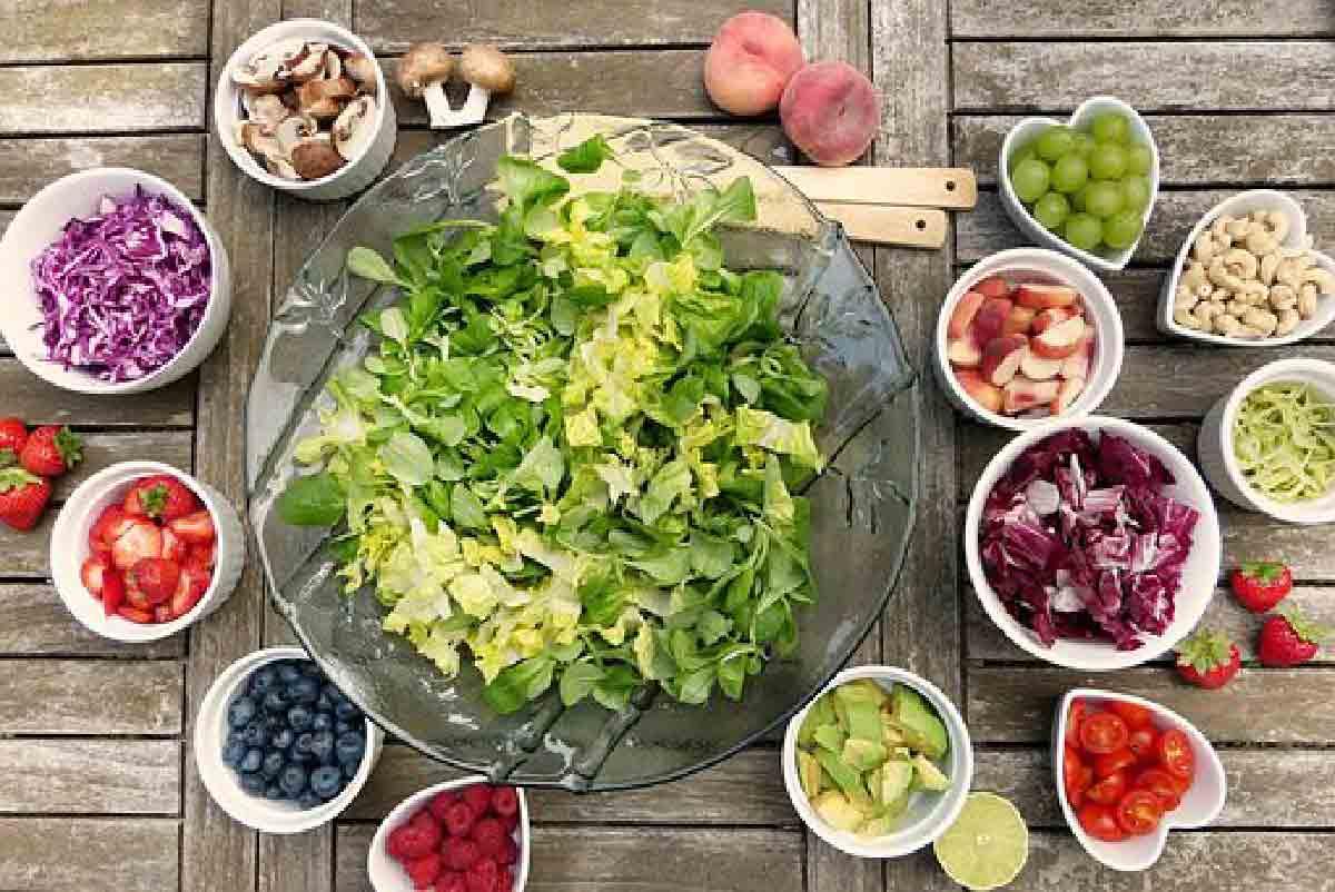 verdure miste in primo piano con contorni di frutta di stagione