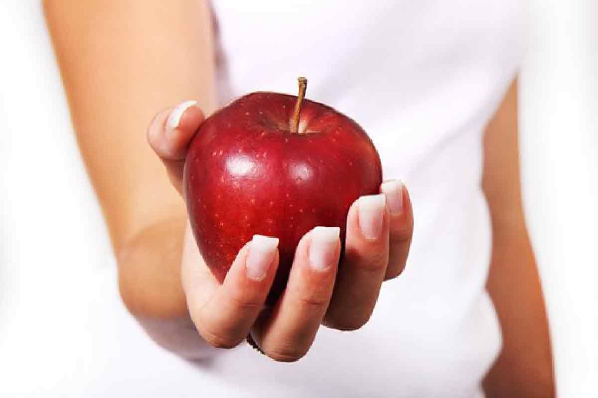 una donna tiene una mela rossa in primo piano