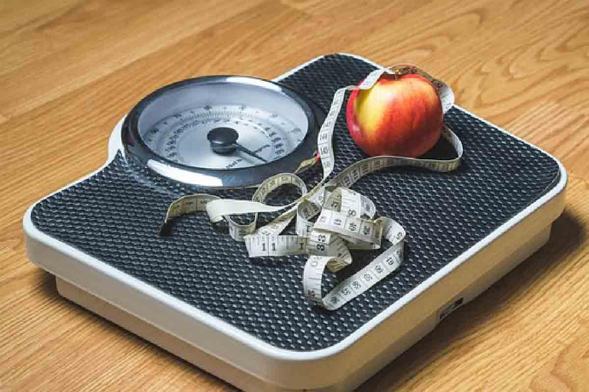 una bilancia ripresa dall'alto con una mela e un metro